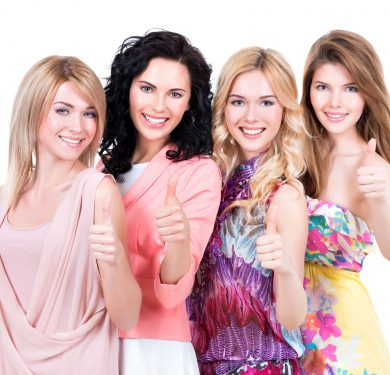 32263093 - group of young beautiful happy women with thumbs up sign posing at studio over on white background.