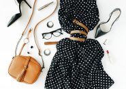 60849299 - flat lay feminini clothes and accessories collage with black dress, glasses, high heel shoes, purse, watch, mascara, lipstick, earrings on white background.